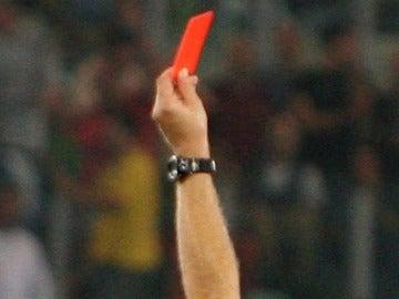 Un árbitro muestra la tarjeta roja