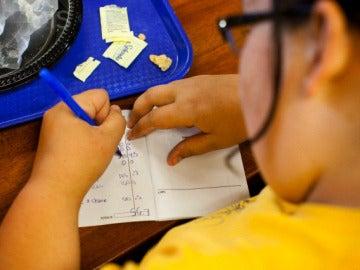 Niño haciendo los deberes después de comer