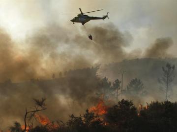 Un helicóptero descarga agua sobre un incendio