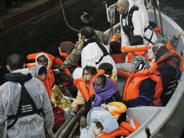 Una barca de salvamento llega al buque anfibio 'San Marco Mare Nostrum' con inmigrantes rescatados.