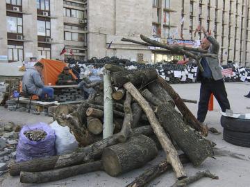 Un manifestante prorruso amontonta madera junto a una barricada