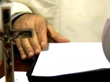 Un religioso con documentos y un crucifijo