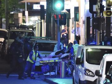 Los servicios médicos atienden a un herido junto a la cafetería de Sidney