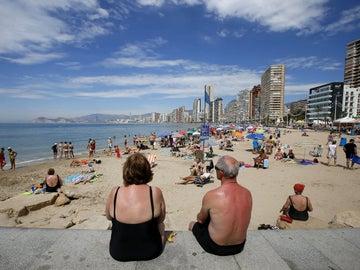 Varios turistas disfrutan de sus vacaciones en la playa.