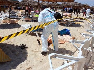 Un policía examina a dos víctimas del ataque terrorista en uno de los hoteles de Susa