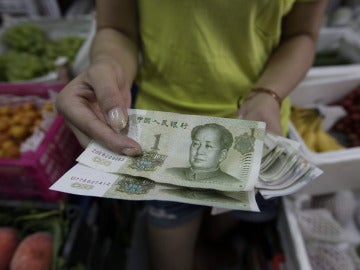 Una mujer muestra billetes de yuan en Pekín