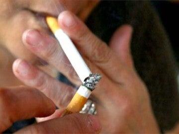 Una persona encendiéndose un cigarro