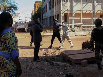 Un rehén es escoltado por personal militar de Mali a su salida del hotel Radisson