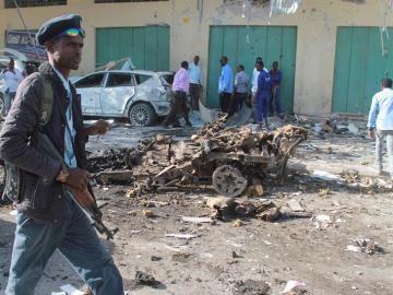 Un oficial de seguridad somalí pasa delante de los restos de un vehículo tras una explosión en Mogadiscio