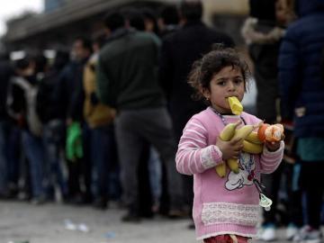 Una niña camina con fruta en las manos mientras muchos otros refugiados esperan comida