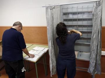 Operarios del Ayuntamiento de Pamplona colocan en un colegio electoral de la capital navarra