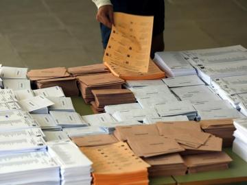 Un votante selecciona las papeletas antes de votar
