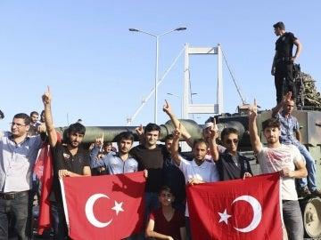 Partidarios del presidente Recep Tayyip Erdogan muestran la bandera nacional junto a un tanque.