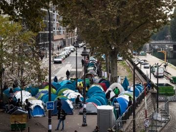 Varios inmigrantes junto a sus tiendas de campaña en un campamento cerca de las estaciones en París, Francia
