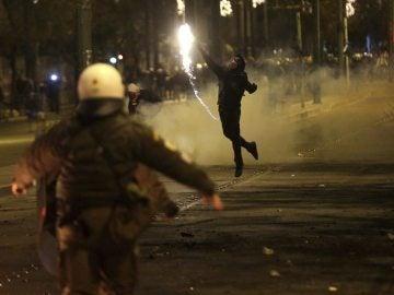 Un manifestante lanza un cóctel molotov contra los policías en Atenas
