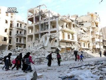 Un grupo de familias sirias desplazadas que abandonan los barrios del este de Alepo