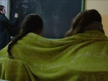 Imagen de dos alumnas dando clase abrigadas con una manta para soportar el frío