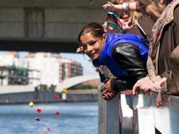 Varias personas tiran pétalos al agua durante la Ceremonia del Río, en la que se simboliza la salida de los antepasados de los gitanos y gitanas de la región del Punjab en la India