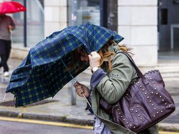 Una mujer intenta sujetar el paraguas que le protege de la lluvia debido al fuerte viento