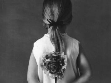 Una niña de espalda con una flor