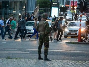 Personas andando junto a un soldado armado en el exterior de la Estación Central