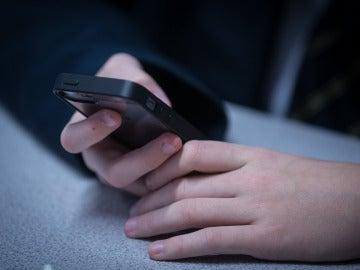 Un niño consulta un teléfono móvil (Archivo)