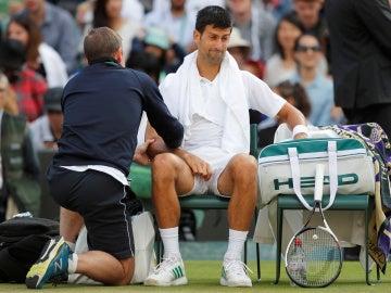 Novak Djokovic, atendido por un fisioterapeuta en Wimbledon