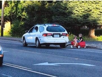 La mujer arrastrando a los niños con su coche