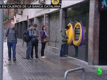 Algunos ciudadanos hacen cola en el cajero automático