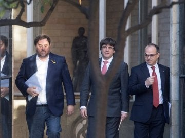 Carles Puigdemont, president de la Generalitat, entre el vicepresident, Oriol Junqueras, y el portavoz del Govern, Jordi Turull