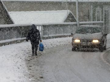 Una vecina del pueblo de Pajares camina entre la nieve