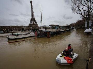 Un hombre transporta a un pasajero en un bote en el desbordado río Sena