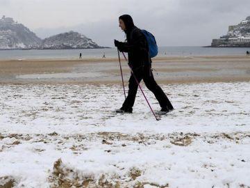 Imagen de archivo de un hombre caminando por la nieve en la Playa de la Concha (San Sebastián)