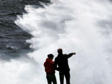 Un grupo de turistas obvervan las olas esta tarde en Muxía, A Coruña