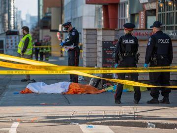 Oficiales de la policía de Toronto vigilan frente al cuerpo de una de las víctimas