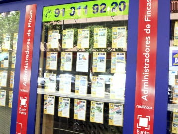 Imagen de archivo de un escaparate de una inmobiliaria en Barcelona, con anuncios de pisos en venta