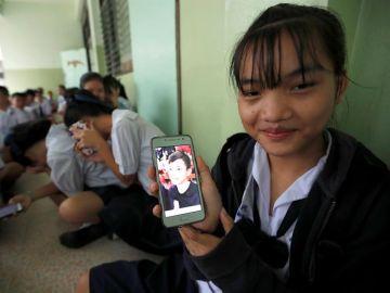 Una estudiante tailandesa muestra una fotografía de su compañero de clase