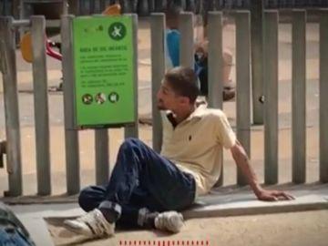 Un toxicomano al lado de un niño jugando