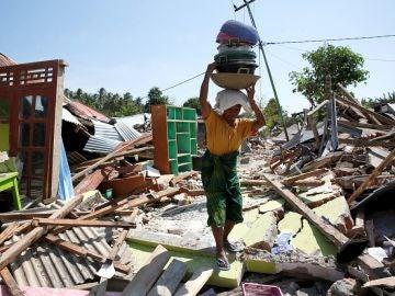 Una mujer carga con sus pertenencias entre los escombros en Lombok