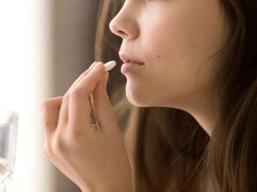 Imagen de una mujer tomando una pastilla.