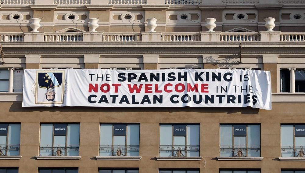 pancarta en contra del rey en la fachada de un edificio de la plaza de Cataluña de Barcelona, donde se va a celebrar el acto central en recuerdo de las víctimas de los atentados del 17A