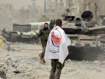 Un soldado del Ejército sirio porta una bandera de la Fuerza de la Defensa Nacional Siria (FDN) en el campamento de Yarmouk, al sur de Damasco