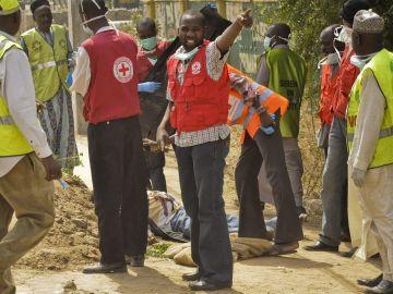 Miembros de la Cruz Roja y de la Agencia Nacional de Emergencias de Nigeria (NEMA), trasladando el cuerpo de una víctima, en la ciudad septentrional nigeriana de Kano