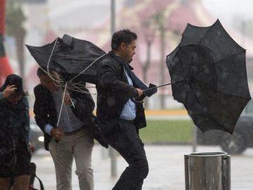 Imagen de archivo: Varias personas sujetan sus paraguas por el fuerte viento.