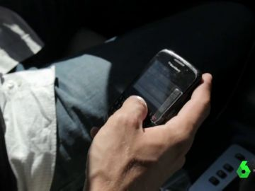 Un conductor utiliza el móvil al volante