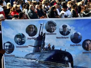 Imagen de un hombre que sostiene una pancarta con imágenes de algunos tripulantes del submarino argentino ARA San Juan