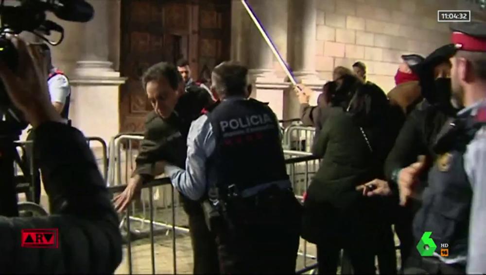 Un grupo de personas intenta descolgar el lazo amarillo de la fachada del Palau