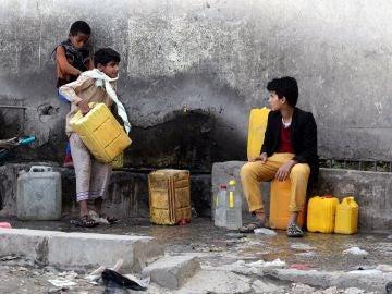 Dos niños yemeníes recogen agua de una fuente en Saná, Yemen.