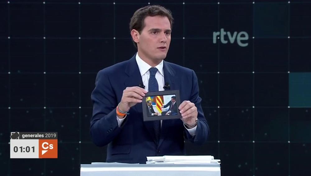 Rivera tira de escenografía: tarjeta sanitaria con la bandera de España y fotos de Torra y Rato para atacar a Sánchez y Casado