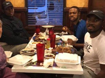 Imagen de tres jóvenes cenando junto a una anciana en Alabama